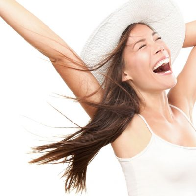 Happy Asian woman with arms in the air holding a hat
