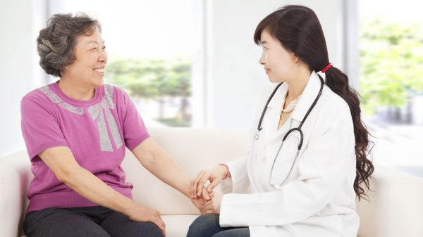 Female Asian Doctor holding elderly Asian woman's hand
